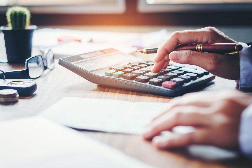 Hände eines Geschäftsmannes mit Taschenrechner, um Kosten zu kalkulieren