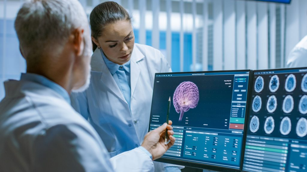 Neurowissenschaftler vor dem PC mit Hirnscans
