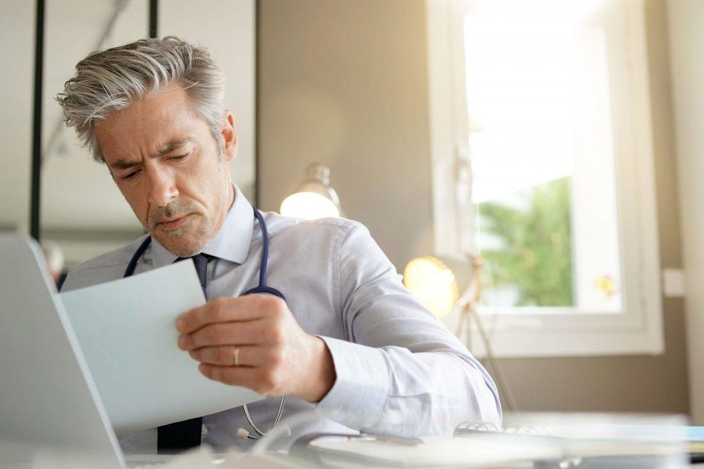 lesender Arzt am Schreibtisch