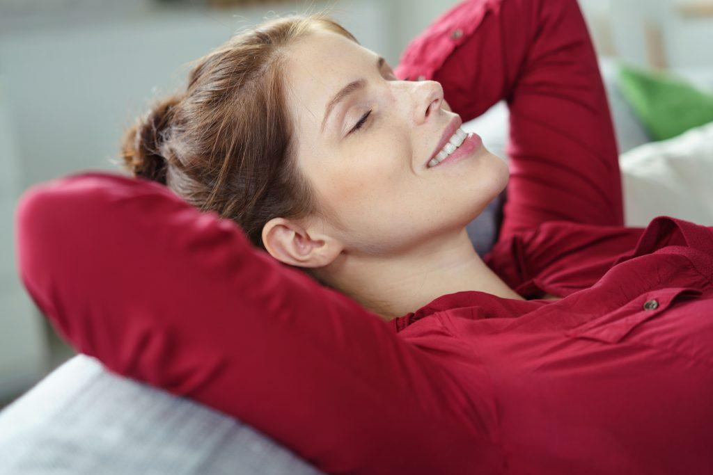 ausruhende, lächelnde Frau mit roter Bluse, die den Ketamin-Dämmerschlaf symbolisiert
